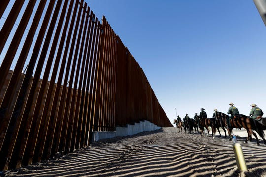 Mounted Border Patrol agents ride along a newly fortified border wall structure in Calexico, California, earlier this year.