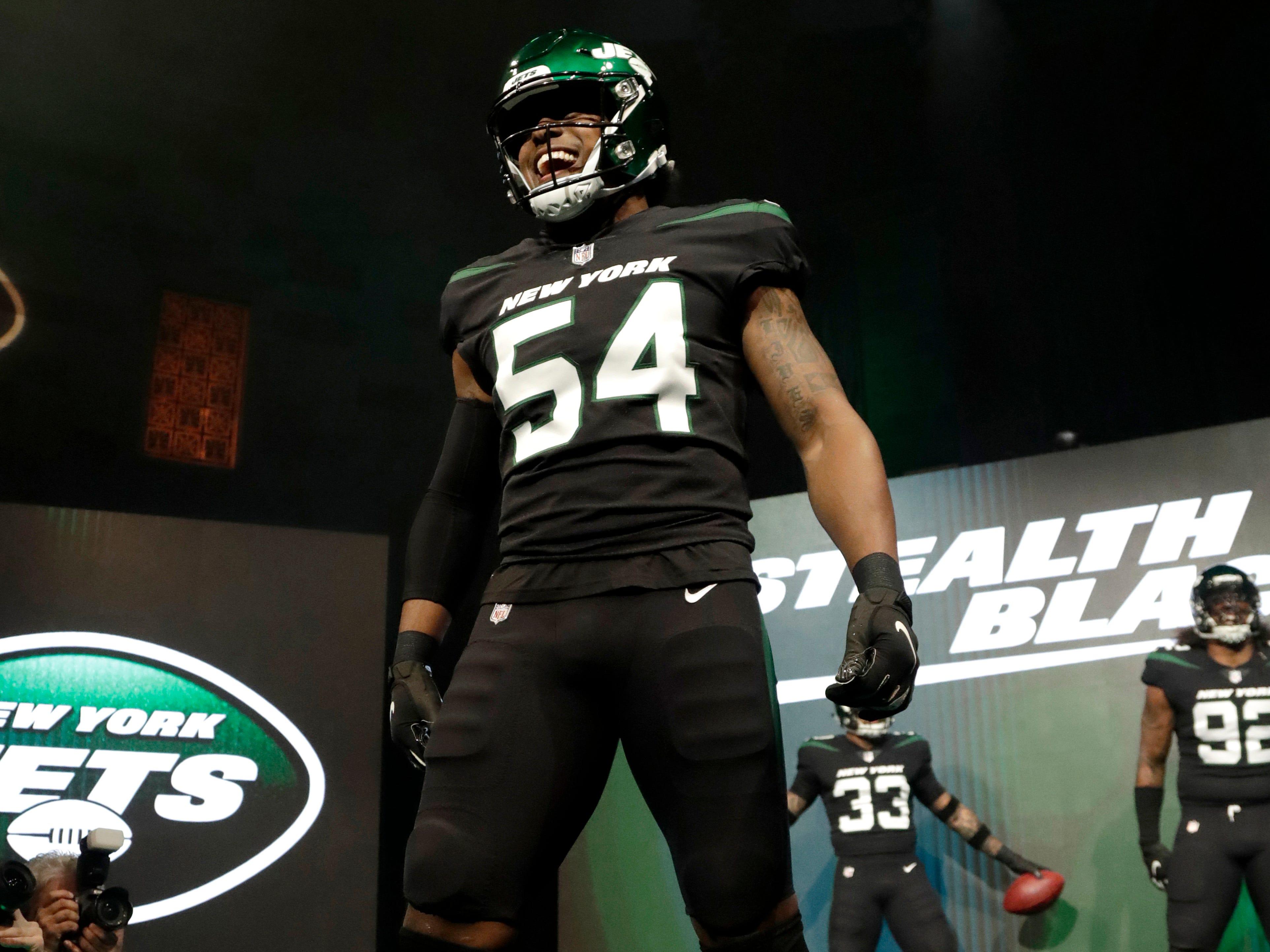 """New York Jets inside linebacker Avery Williamson models the team's new """"stealth black"""" uniform."""