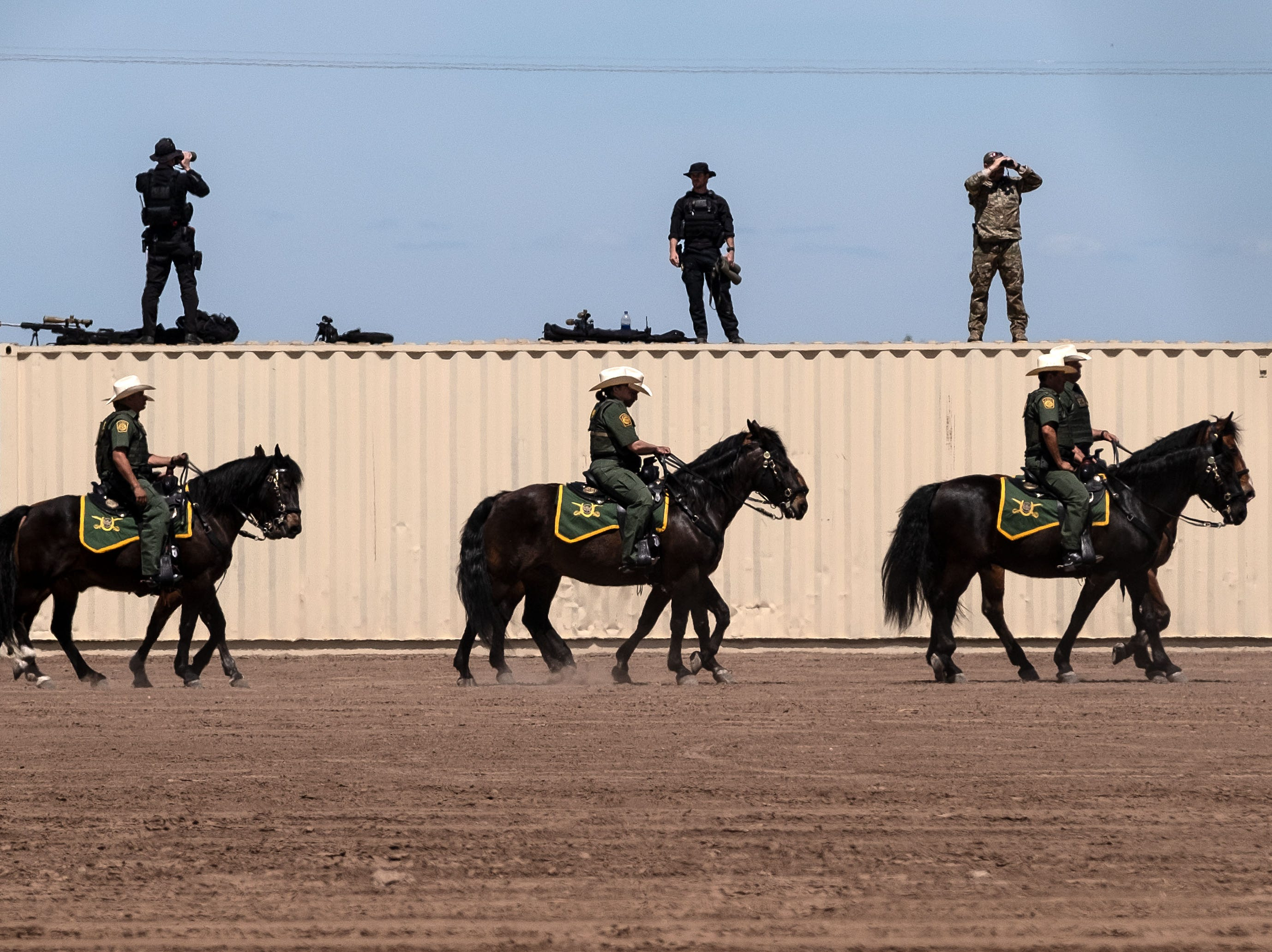 Members of the US secret service and border patrol agents on horseback, patrol near the US-Mexico border fence in preparation for the visit of US President Donald Trump to Calexico, Calif., as seen from Mexicali, Baja California state, Mexico, on April 5, 2019.