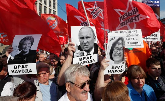 Supporters of Russian Communist party hold portrait of Russian Federation Council Chairman Valentina Matvienko (L), Russian President Vladimir Putin (C) and Head of the Russian Central Bank Elvira Nabiulina (R) with slogan read as 'Enemy of the people' during a protest rally against government's proposed pension reform plan in Moscow,  September 22, 2018. Putin supported government's proposal to increase retirement age for men to 65 from the current 60 and for women to 60 from the current 55.