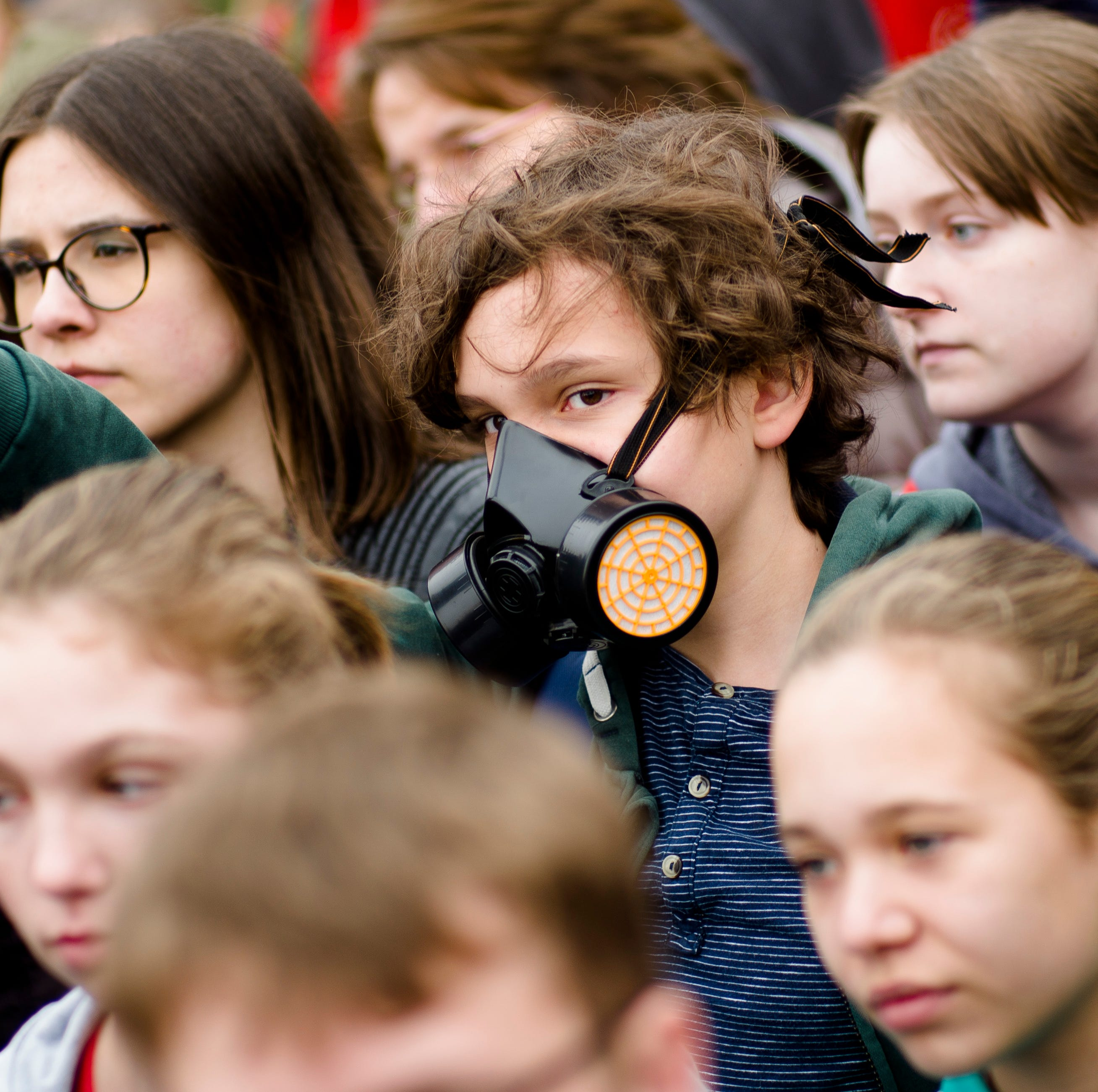 A boys wears a respiratory protection mask as he attends a students climate strike as part of the Friday's For Future movement in Berlin, Friday, April 5, 2019.