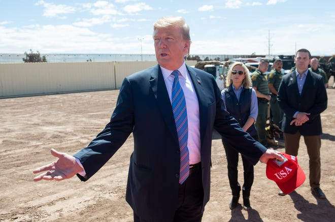 President Donald Trump speaks with members of the US Customs and Border Patrol as he tours the border wall between the United States and Mexico in Calexico, Calif. on April 5, 2019. President Donald Trump landed in California to view newly built fencing on the Mexican border, even as he retreated from a threat to shut the frontier over what he says is an out-of-control influx of migrants and drugs.