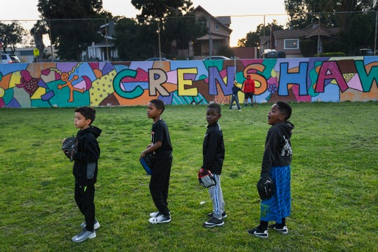 Members of the Van Ness Padres youth baseball team practice at Crenshaw High School in Los Angeles on April 3, 2019.