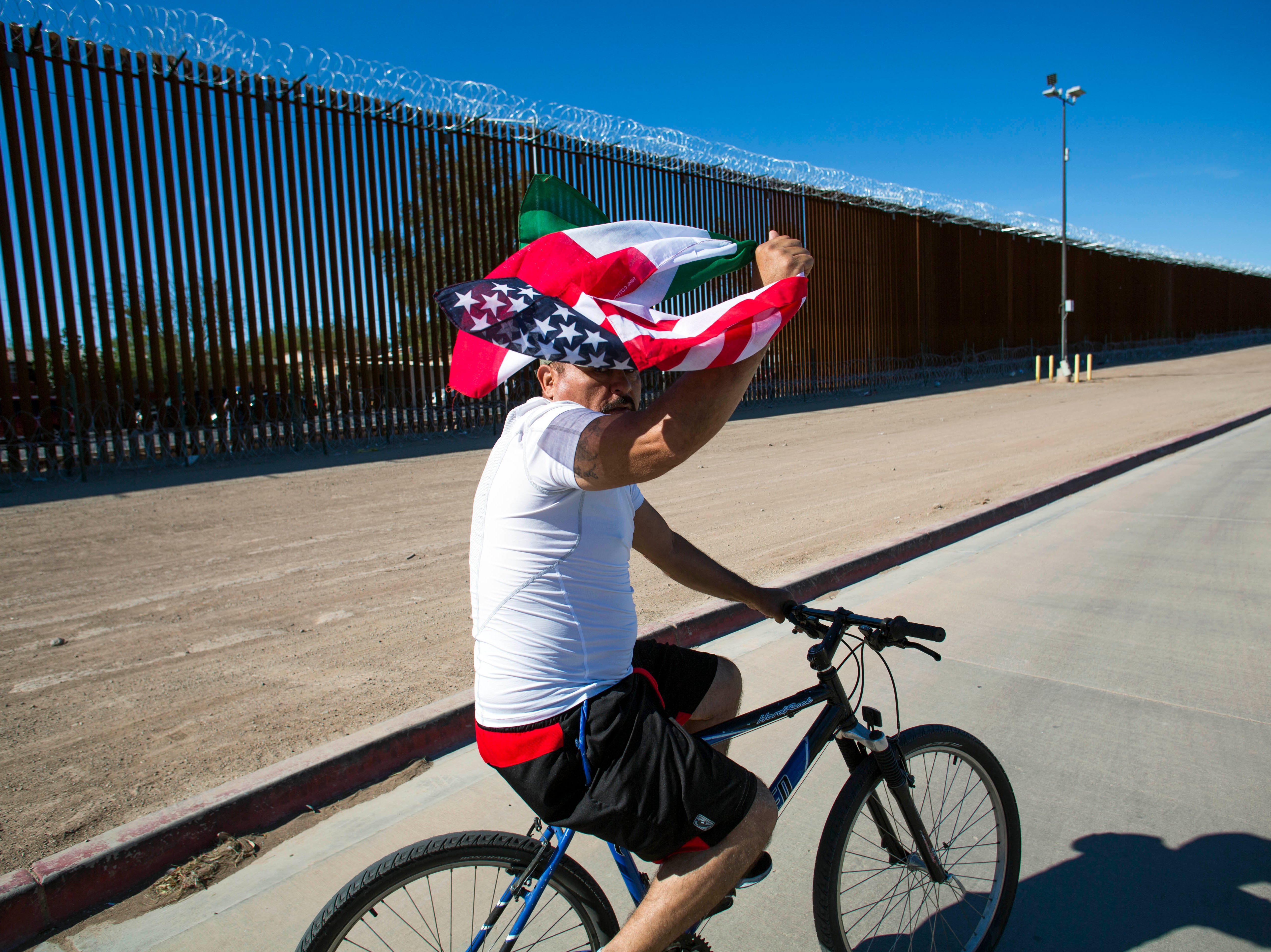 A man holding a U.S. and Mexican flags rides his bikes a few feet from the wall separating Mexico and the U.S. during the Binational March of Unity in Calexico, Calif. The march was organized by as a response to President Donald Trump's visit to the border town. The march of over 100 people was composed of members from Mexicali, Mexico and Calexico, California.
