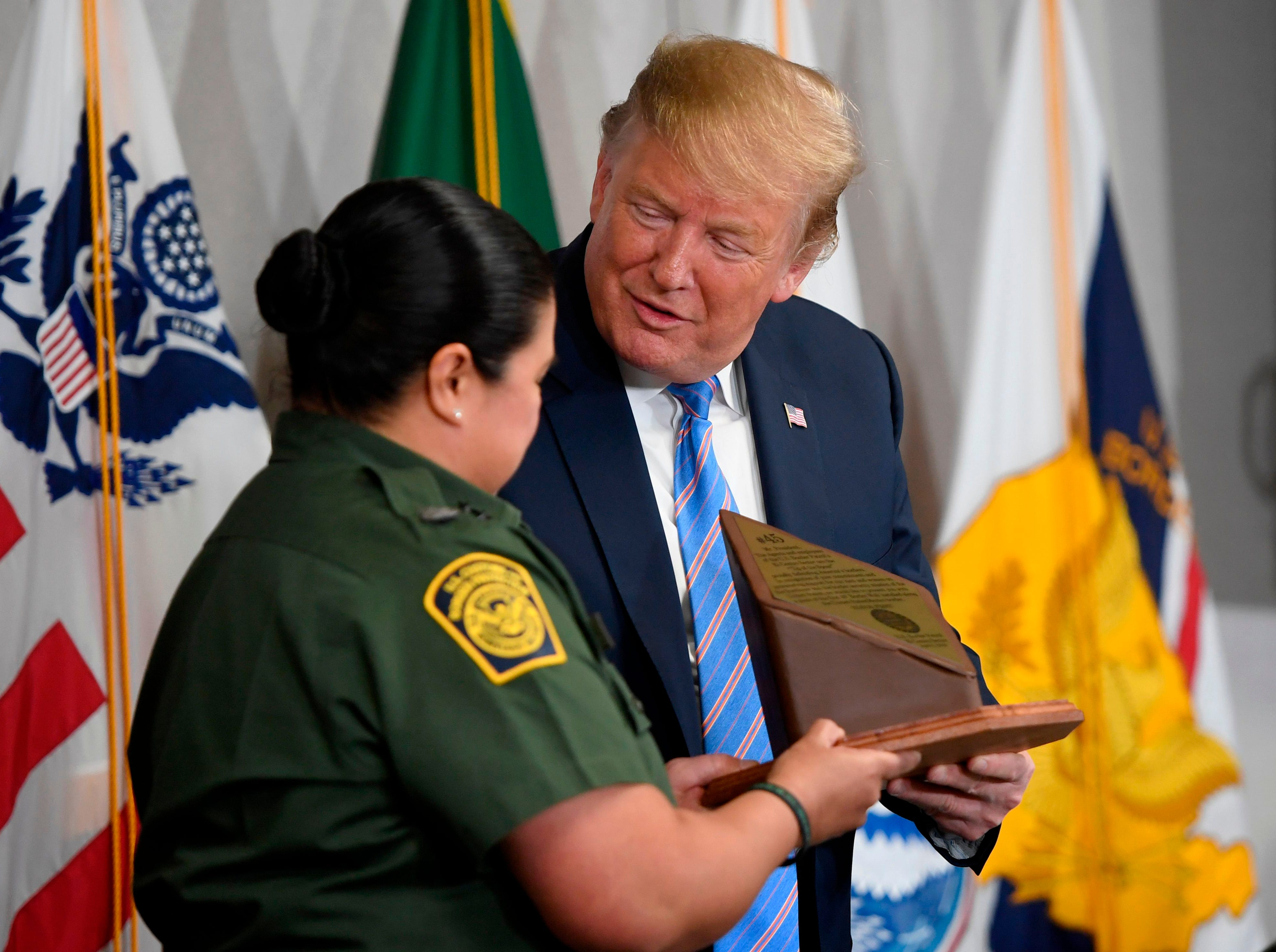President Donald Trump is given a piece of the border wall from Customs and Border Patrol Chief Patrol Agent Gloria Chavez during a roundtable on immigration and border security at the US Border Patrol Calexico Station in Calexico, California, April 5, 2019.