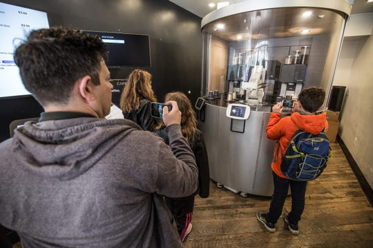 "Customers watch a robot make coffee drinks at Cafe X in downtown San Francisco. The company has three locations in the Bay Area, and soon will open up at the local airport. Founder Henry Hu says offloading the task of ""pushing coffee machine buttons"" to robots frees up humans to consult with customers on their order."