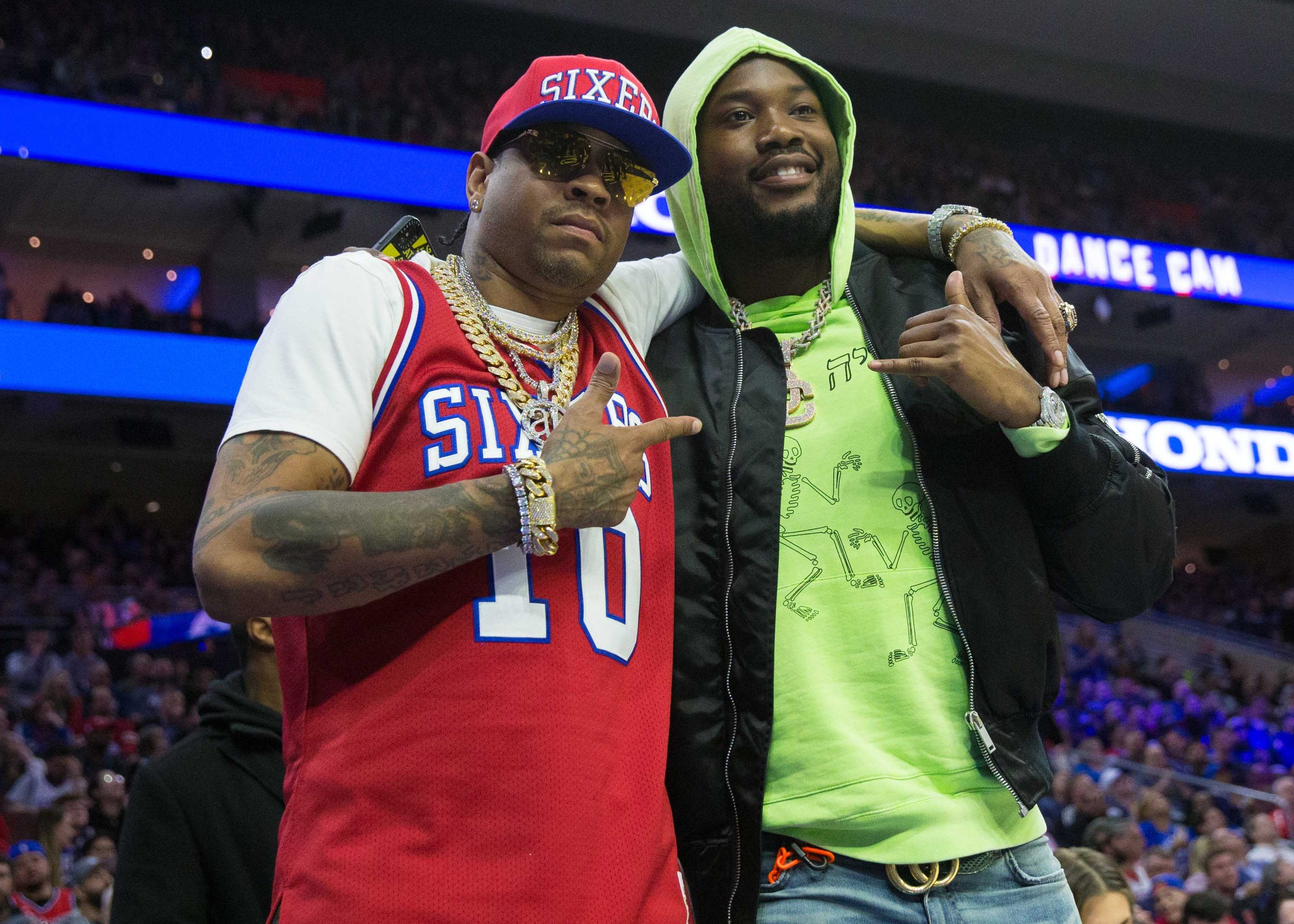 April 4: Allen Iverson, left, and Meek Mill take in the 76ers-Bucks game in Philadelphia.