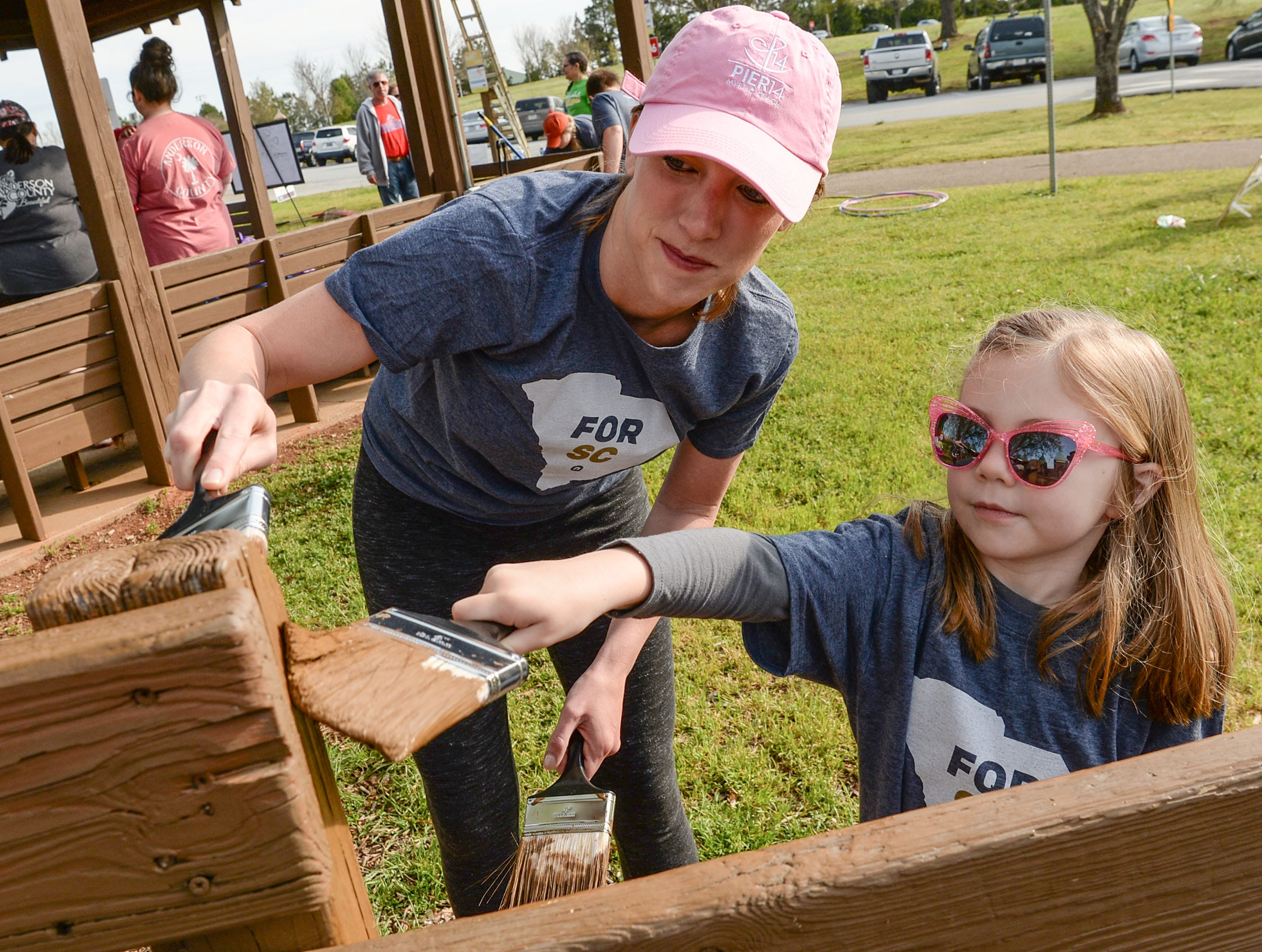 Katie Laughridge, left, and her daughter Cora, 4, stain a fence during KidVenture cleanup day at the Anderson Sports and Entertainment Complex Saturday. A group of 310 volunteers, 250 from NewSpring Church, helped spread 100 cubic yards (70,000 pounds) of mulch, and brush 30 gallons of stain on the fences, pick up trash, and trim trees and shrubs at the park which opened 20 years ago in 1999.
