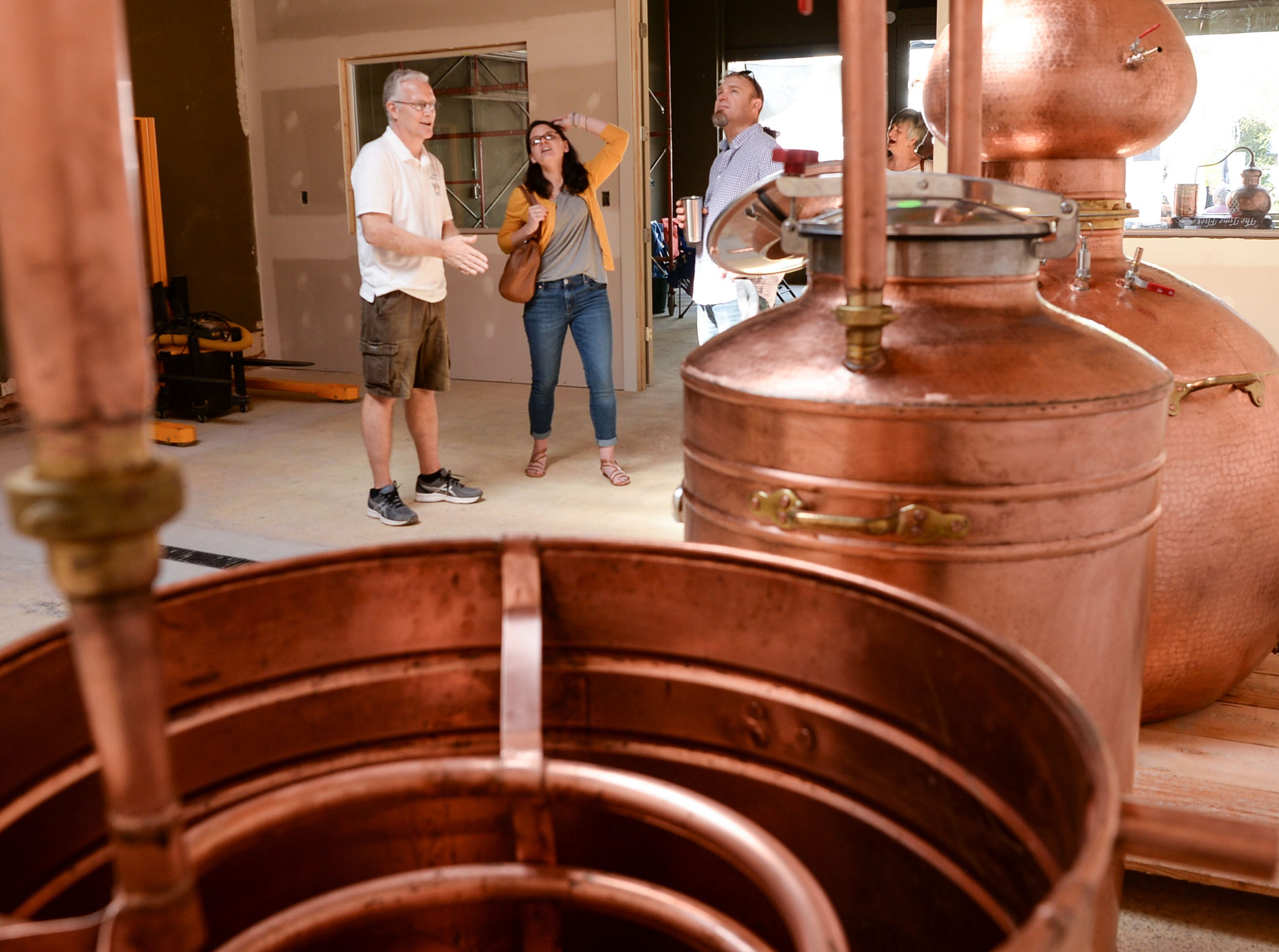 Ernie Wagner, co-owner of Swamp Fox Distilling, talks to visitors as the store prepares to open in a few months, on display during the Spring Jubilee in Historic Pendleton Saturday.