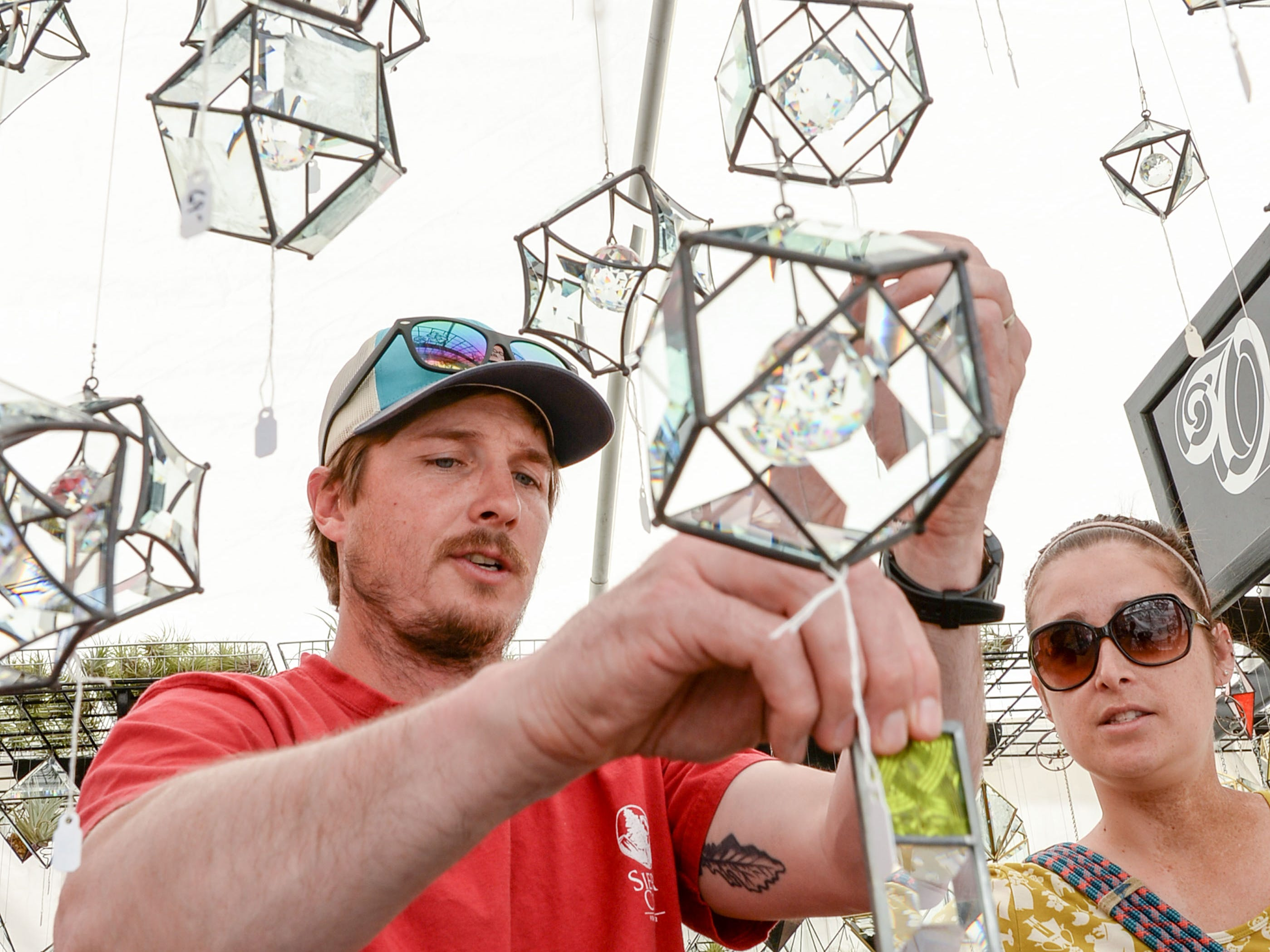 Tyler Hollingsworth and sister-in-law Meghan Hollingsworth, right, look at Oriskany Glass Studio art during the Spring Jubilee in Historic Pendleton Saturday.