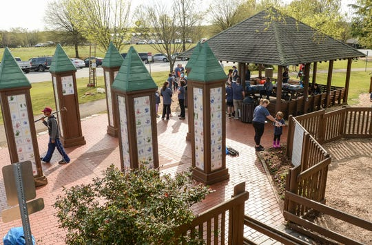 Adults and children spread mulch during KidVenture cleanup day at the Anderson Sports and Entertainment Center. A group of 310 volunteers, 250 from NewSpring Church, helped spread 100 cubic yards of mulch, and brush 30 gallons of stain on the fences, pick up trash, and trim trees and shrubs at the park, which opened 20 years ago in 1999.