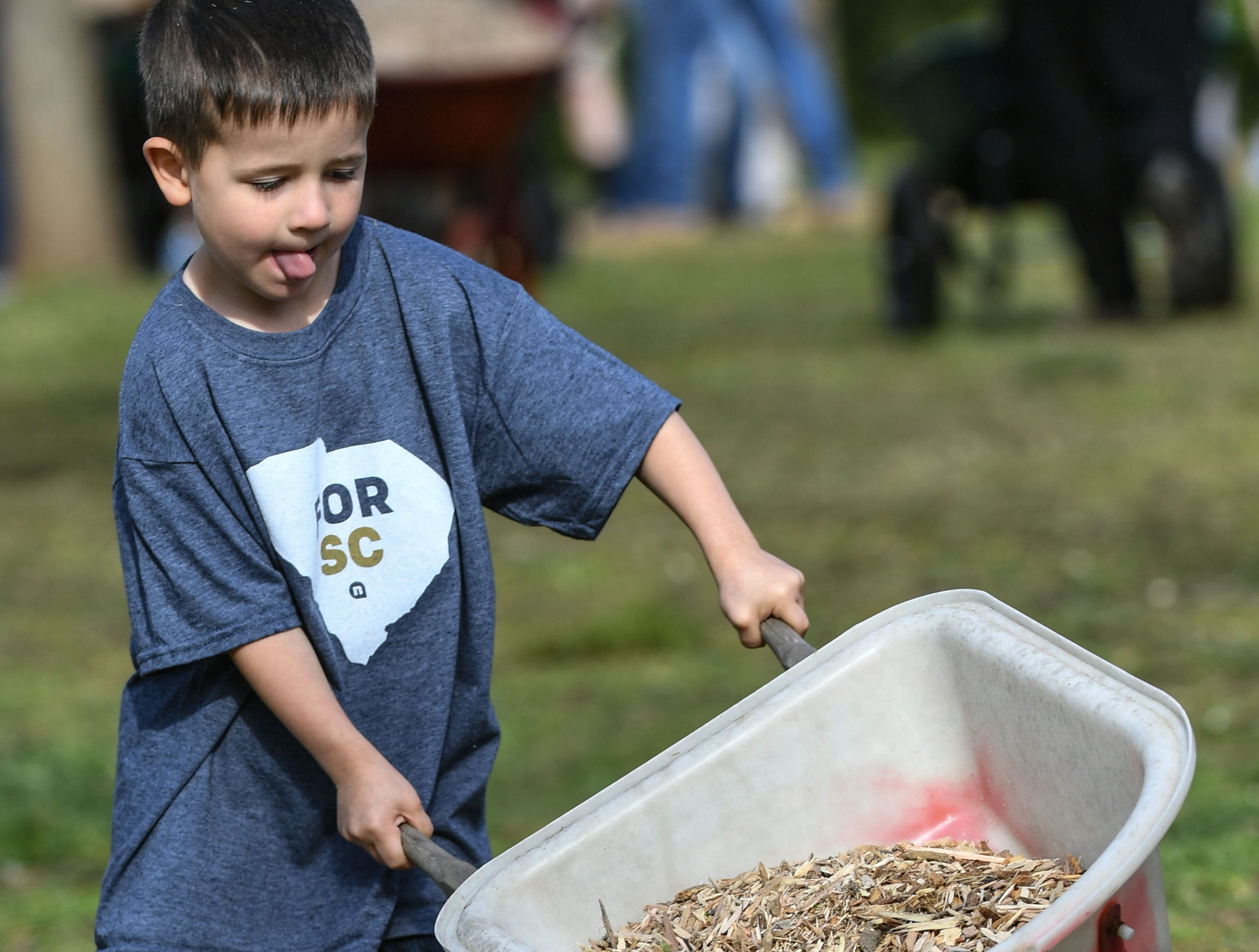 Volunteer Levi Dunagan from NewSpring Church in Anderson helps spread mulch with his miniature wheelbarrow during KidVenture cleanup day at the Anderson Sports and Entertainment Complex Saturday. A group of 310 volunteers, 250 from NewSpring Church, helped spread 100 cubic yards (70,000 pounds) of mulch, and brush 30 gallons of stain on the fences, pick up trash, and trim trees and shrubs at the park which opened 20 years ago in 1999. Across South Carolina, the church helped with community cleanup and beautification, including 12 locations in Anderson County Saturday.