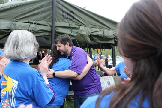 Preston Mansour (right) hugs Jessica Glorioso on Saturday after receiving a plaque from her and her family. Mansour left the Family Justice Center of Central Louisiana recently to return to private legal practice.