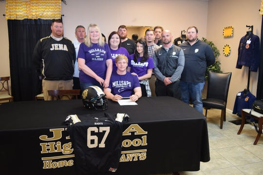 Jena High School senior offensive lineman Casey Spicer (seated) signed with Millsaps Thursday. From left are: Assistant Principal and Coach Adam Powell, Coach Matt Mason, Bernadette Spicer, Hannah Spicer, Coach Matt Danna, Taylor King, Coach Ikey Ray, Coach Russell Dorton, Head Coach Jay Roark, and Coach Colton Knuckols