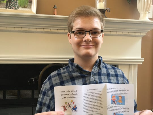 """Tim Rohrer holds up his guide, """"How to be a good influence to people with disabilities."""""""