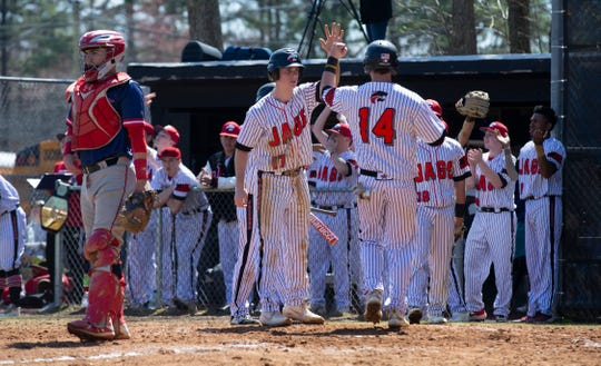 Jackson Memorial's Carmine Petosa gets a high five from Tom Cartnick as he crosses the plate for his team's fourth run of game. Jackson Liberty Baseball vs Jackson Memorial in a Strikeout for Autism game in Jackson on April 6, 2019.