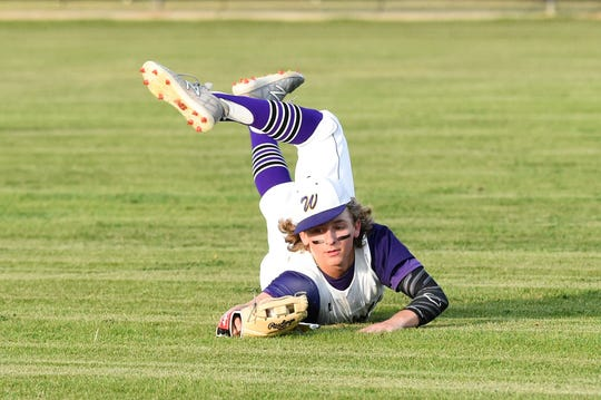 Wylie right fielder Cooper Cothran (21) checks his glove for the ball after making a diving catch against Aledo. The catch ended the game as the Bulldogs held on for a 10-8 victory.