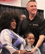 Rob Gass, a former Dyess Air Force Base commander now with Boeing, presented five awards Saturday to families at the World's Largest Barbecue. The biggest was Family of the Year of the Ogletree family, represented by Paula Johnson (mother of TSgt. Olivia Ogletree, left) and the Ogletrees' daughter, Azrvel, center.