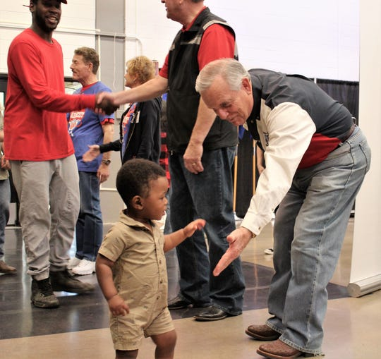 Former Abilene mayor Norm Archibald leans low to welcome Dejeir Applewhite, 14 months, to his first World's Largest Barbecue on Saturday at the Abilene Convention Center. Dejeir was there with his father Darius, left, and his mother, Airman Dominique Applewhite. They are from Florida.