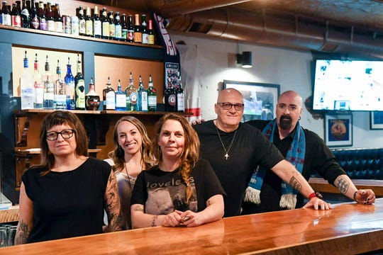 From left, Catie Conroy, Samantha Neesly, Amber Arthur, Steve Hedrick and Daryl Tyler stand behind the bar at Olde London Pub April 4, 2019.
