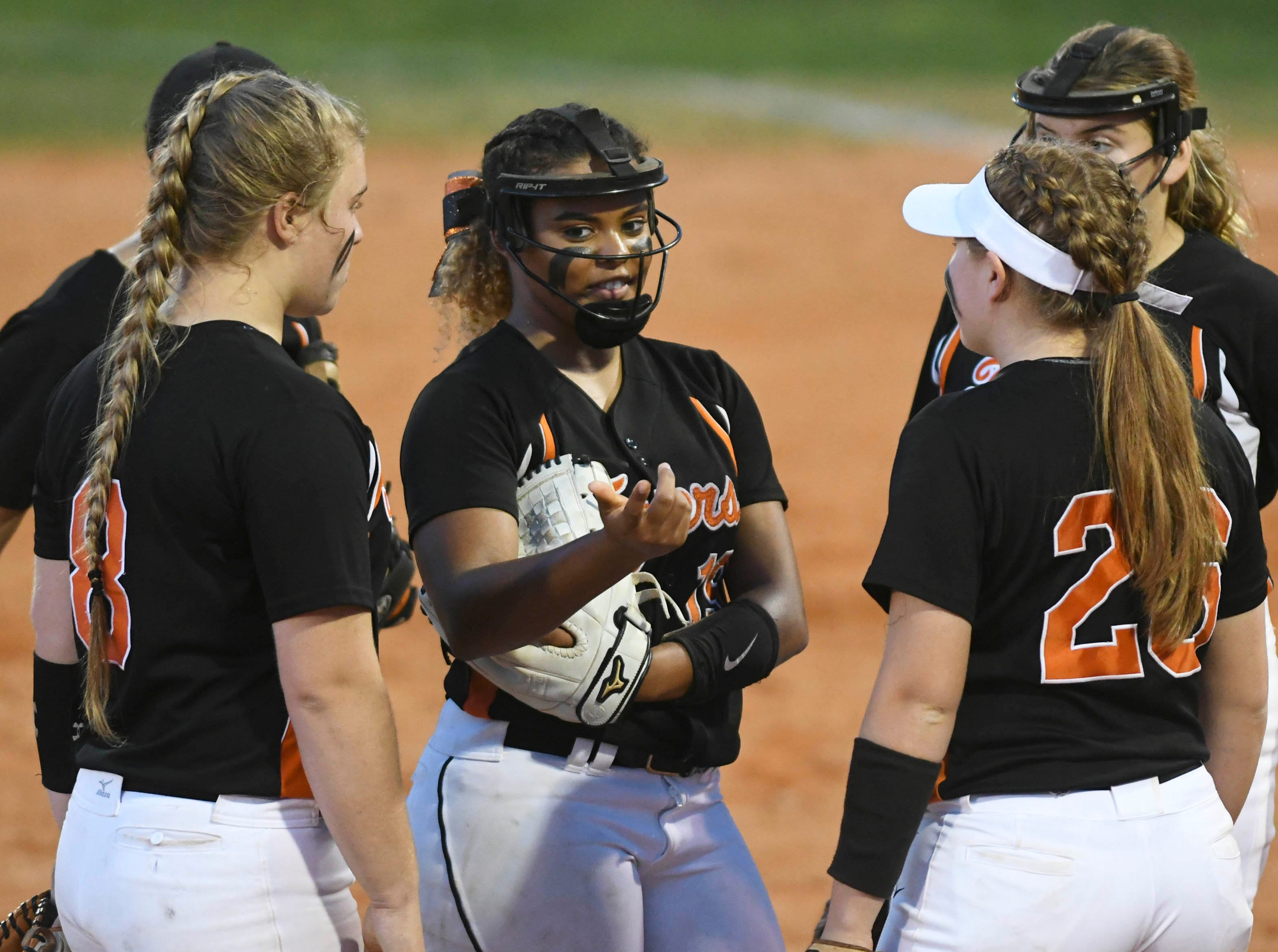 Cocoa players have a conference at the pitchers mound during Friday's game.