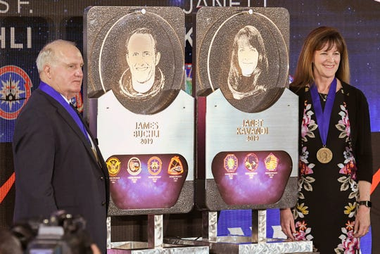 US Astronaut Hall of Fame inductees James F. Buchli and Janet L. Kavandi stand with their likenesses during ceremonies Saturday at Kennedy Space Center Visitor Complex.