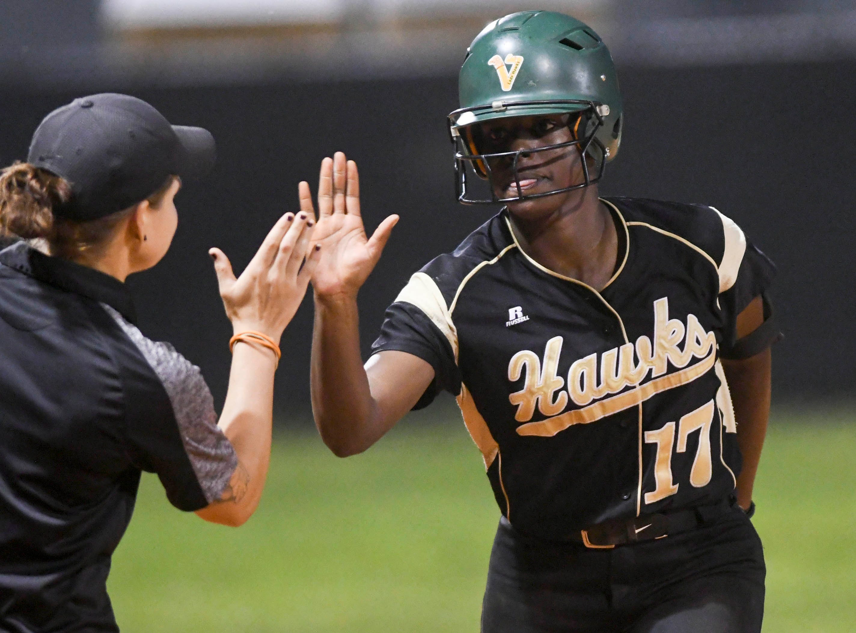 Viera softball head coach Alex Breeden high fives Karyana Mitchell after she hit a home run in Friday's game against Cocoa.