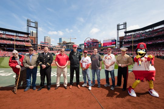 Jeffrey Guarino, fifth from right, is on the field with Fredbird of the St. Louis Cardinals on Saturday as a military tribute took place at Busch Stadium before the Padres-Cardinals game. Guarino's father, Lawrence, spent more than seven years in a Hanoi prison camp.