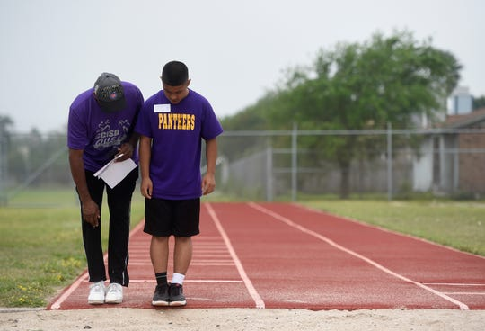 A Special Olympics volunteer shows Andrew Gonzalez where to stand before the long jump, Saturday, April 6, 2019, at Hornet Stadium.