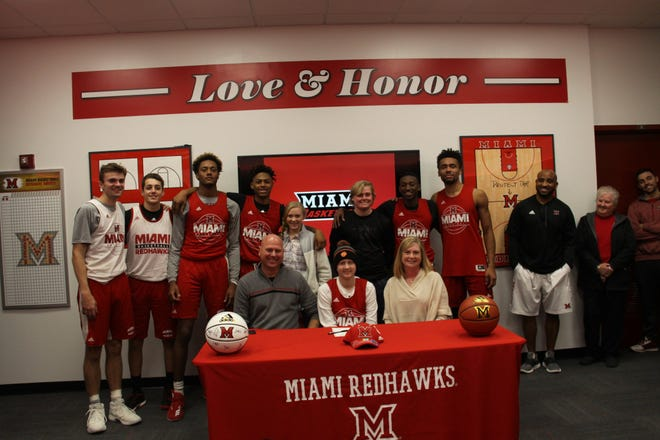 Jackson Hogenkamp and his parents, at the Miami RedHawks' adoption of the 14-year-old from Minster, Ohio, in December of 2017.