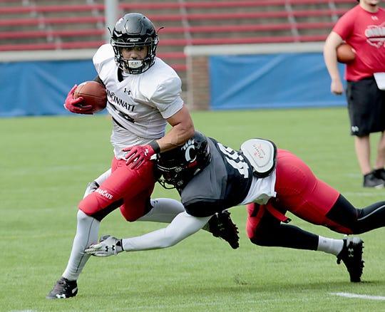 UC running back Ryan Montgomery is tackled by linebacker DeMarco Baker during practice at Nippert Stadium in Cincinnati Saturday, April 6, 2019.