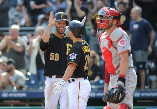 Apr 6, 2019; Pittsburgh, PA, USA; Pittsburgh Pirates base runners Jacob Stallings (58) and Adam Frazier (26) celebrate after scoring in the sixth inning near Cincinnati Reds catcher Curt Casali (12) at PNC Park. Mandatory Credit: Philip G. Pavely-USA TODAY Sports