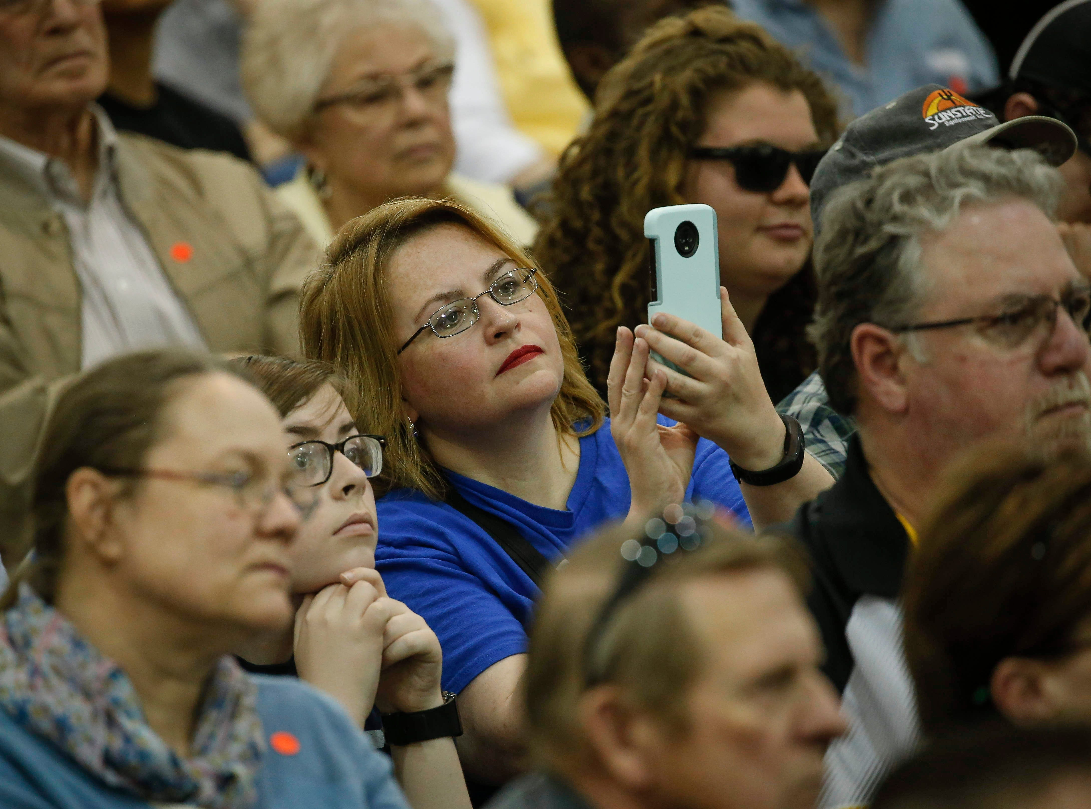 A supporter of Democratic presidential hopeful Bernie Sanders snaps a cell phone photo as he speaks during a town hall style meeting at West Middle School in Muscatine on Saturday, April 6, 2019.