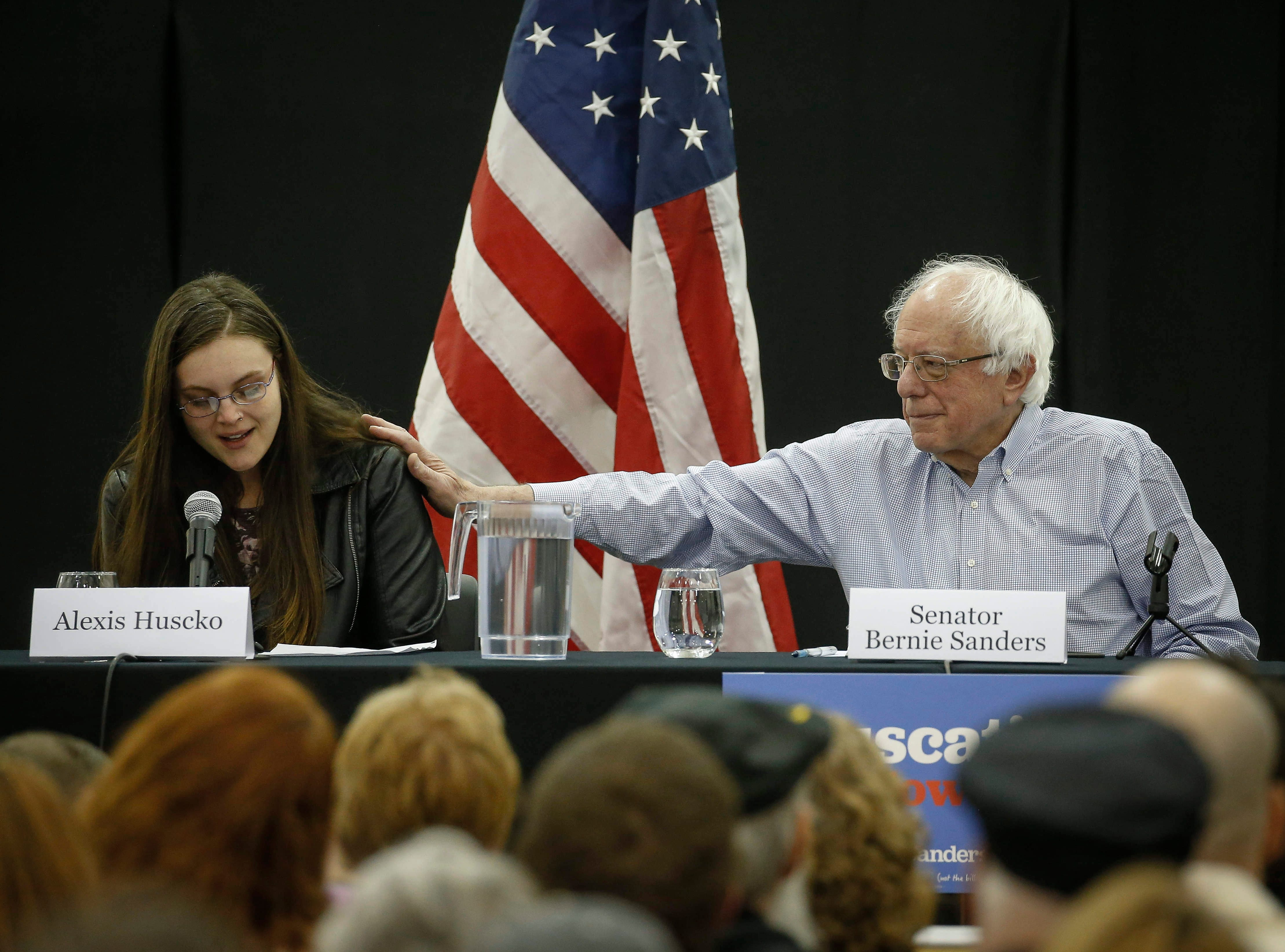 Democratic presidential candidate hopeful and U.S. Sen. Bernie Sanders reaches over to comfort Alexis Huscko of Muscatine as she shares a personal story of battling mental health issues during a town hall meeting at West Middle School in Muscatine on Saturday, April 6, 2019.