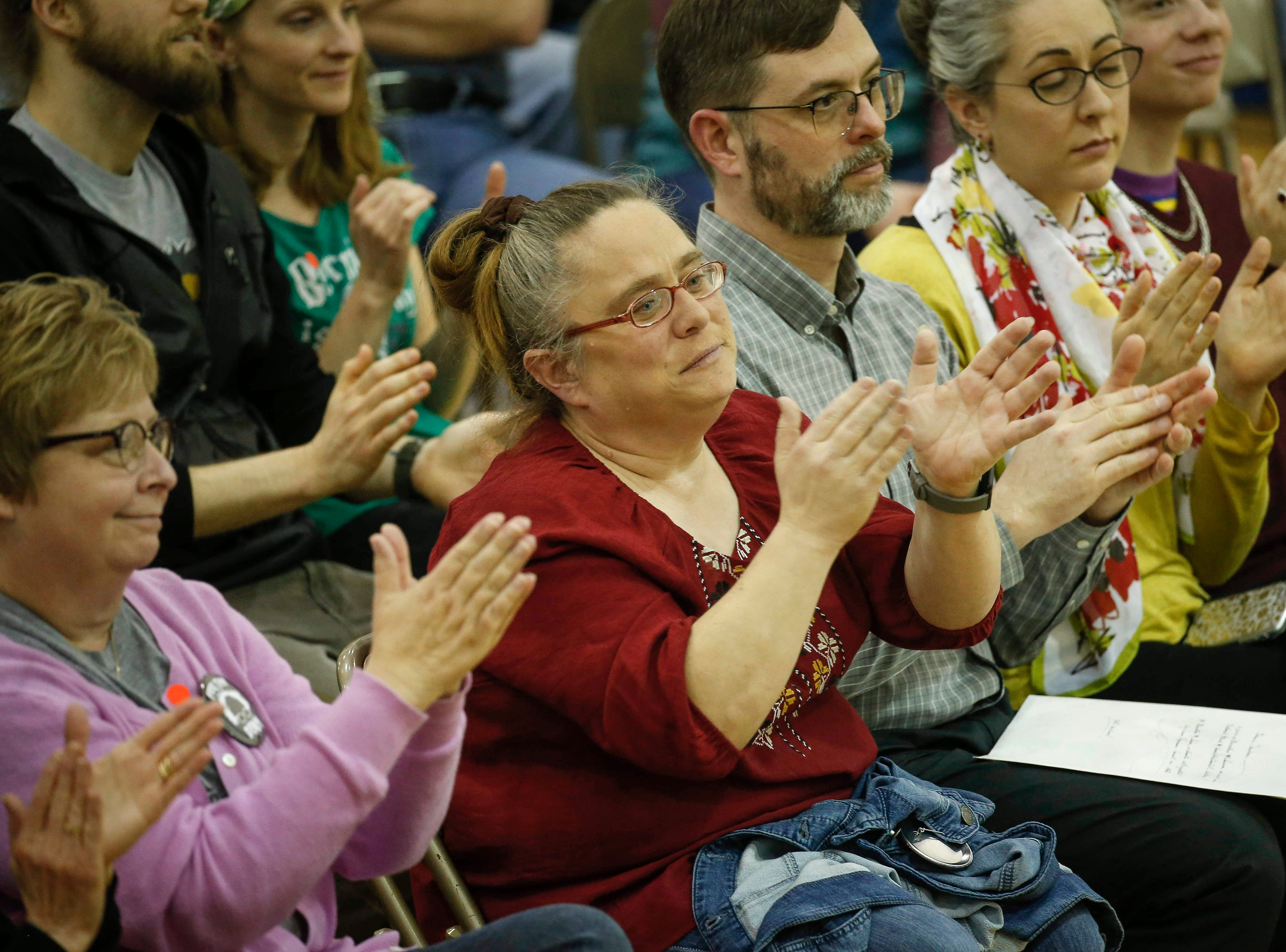 Supporters of Democratic presidential hopeful Bernie Sanders applaud as he speaks during a town hall style meeting at West Middle School in Muscatine on Saturday, April 6, 2019.