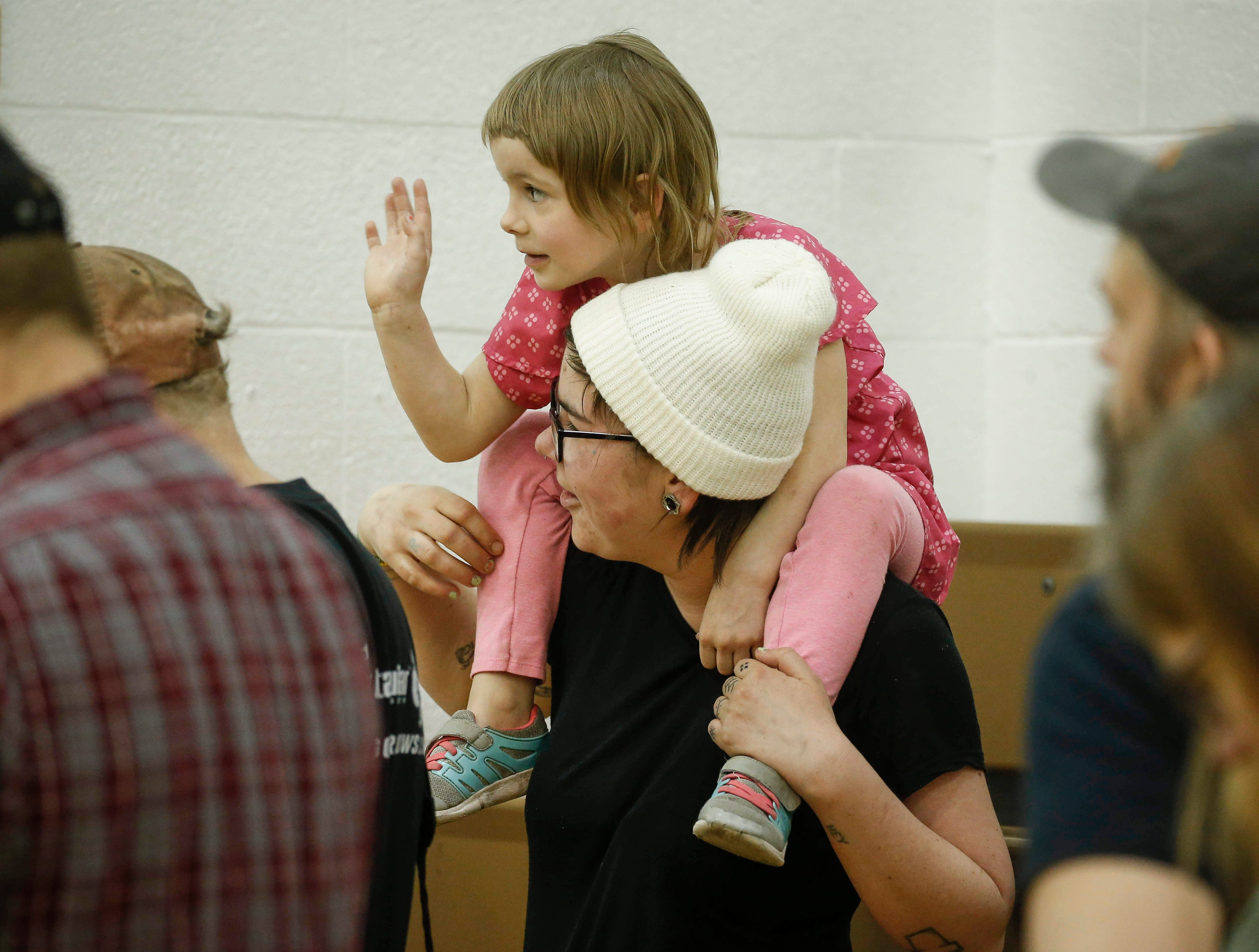 A young girl waves to U.S. Sen. Bernie Sanders as he speaks during a town hall style meeting at West Middle School in Muscatine on Saturday, April 6, 2019.