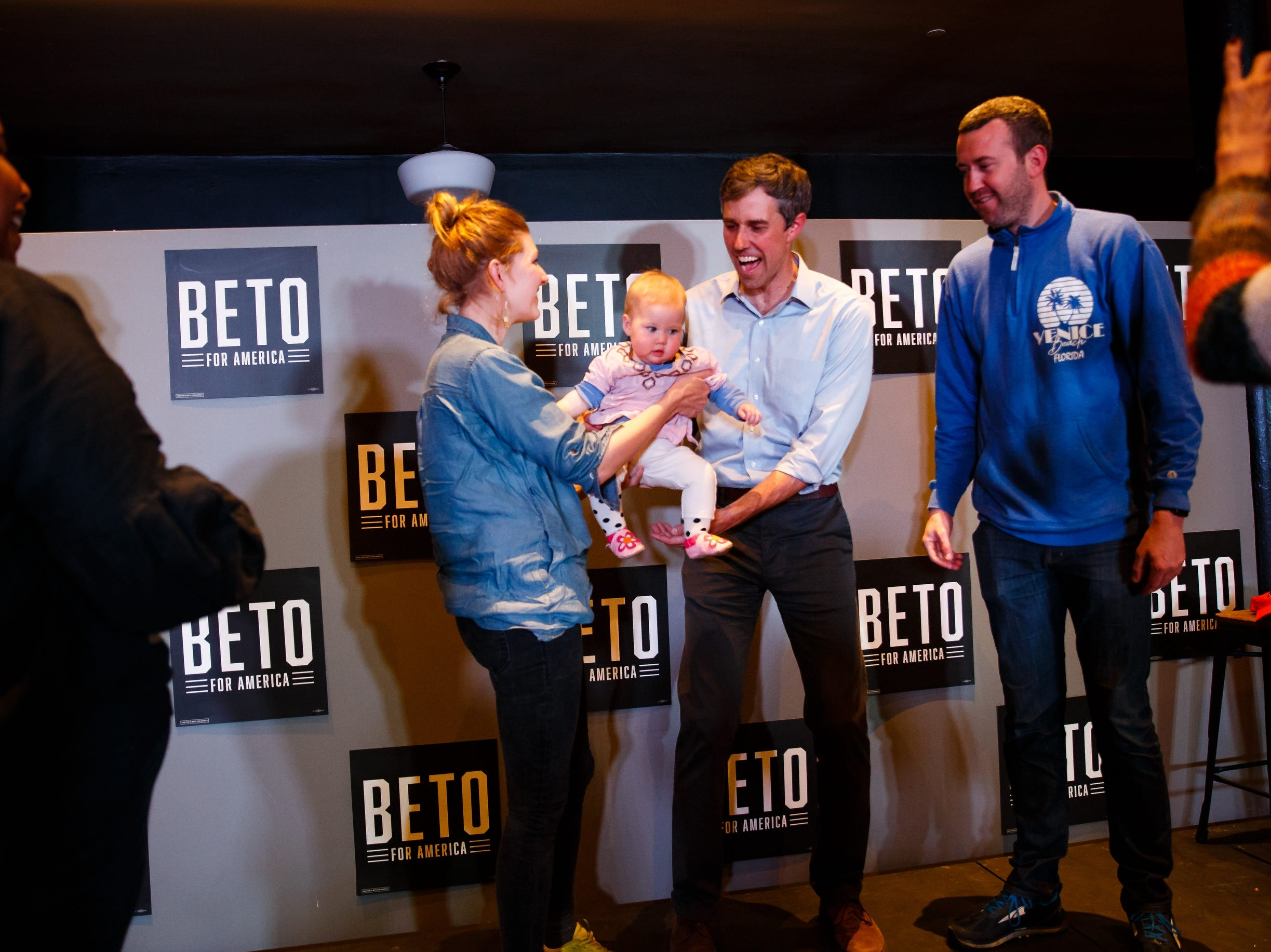 Carrie Ferguson, left, hands 2020 Democratic presidential candidate and former Texas Representative Beto O'Rourke her 7-month-old daughter Fleur as father Ryan looks on after hearing O'Rourke speak at Hotel Grinnell on Friday, April 5, 2019, in Grinnell.