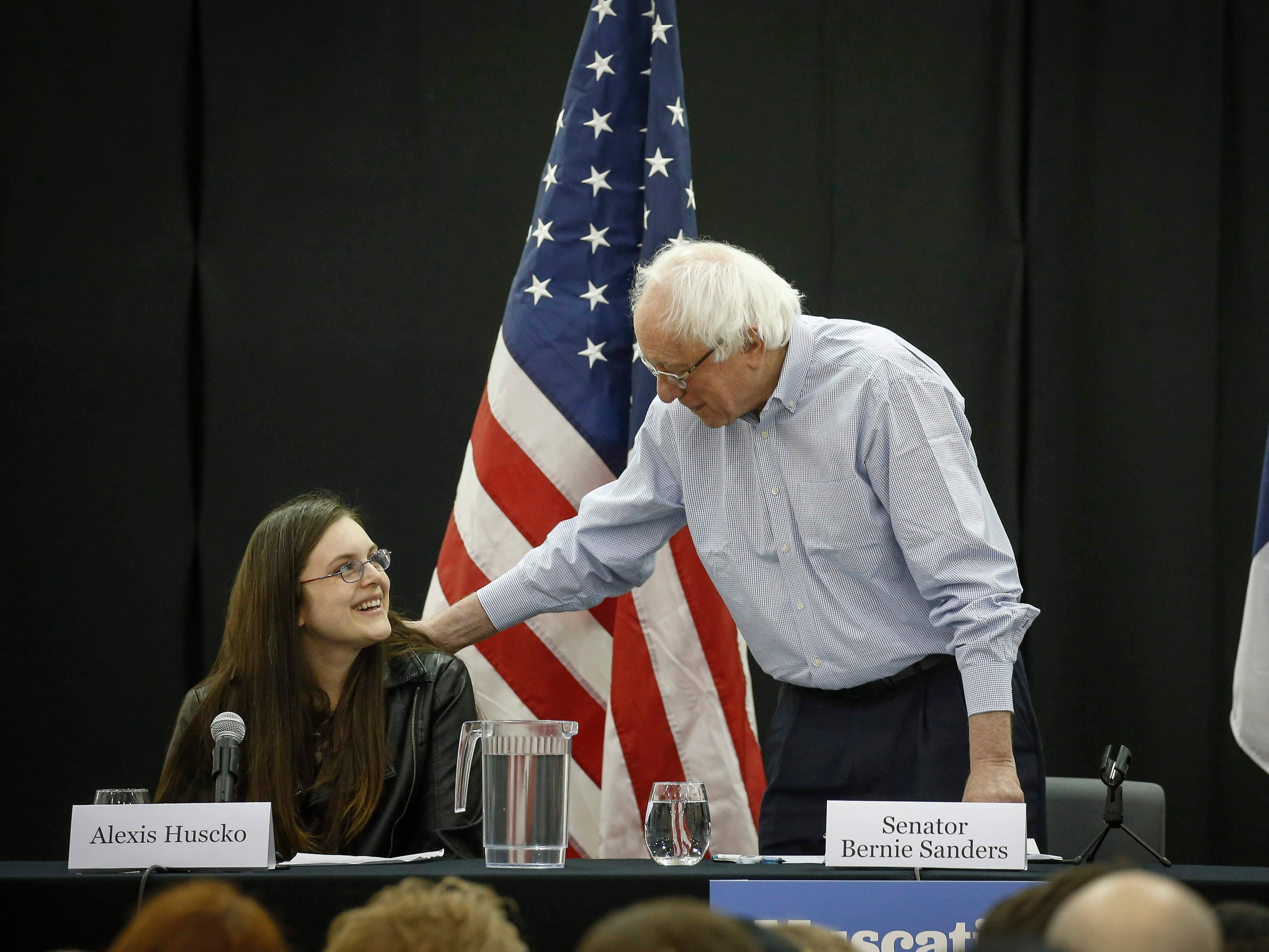 Democratic presidential candidate hopeful and U.S. Sen. Bernie Sanders reaches over to comfort Alexis Huseko of Muscatine as she shares a personal story of battling mental health issues during a town hall meeting at West Middle School in Muscatine on Saturday, April 6, 2019.