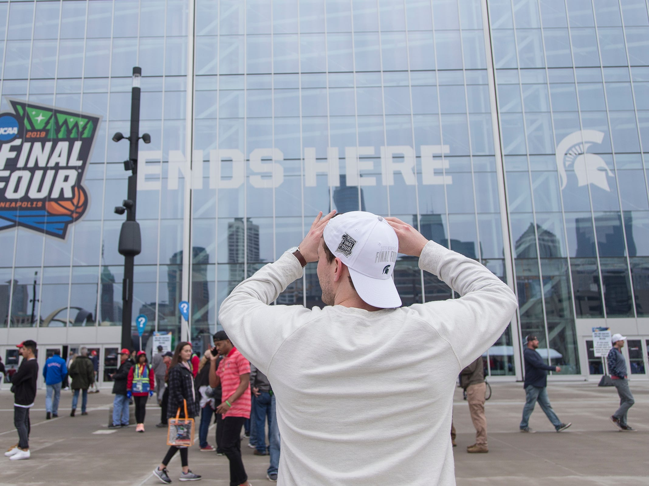 Michigan State alumnus John Venn of Milwaukee, Wis., takes a photo outside of the U.S. Bank Stadium in Minneapolis before the Final Four game against Texas Tech , Saturday, April 6, 2019.