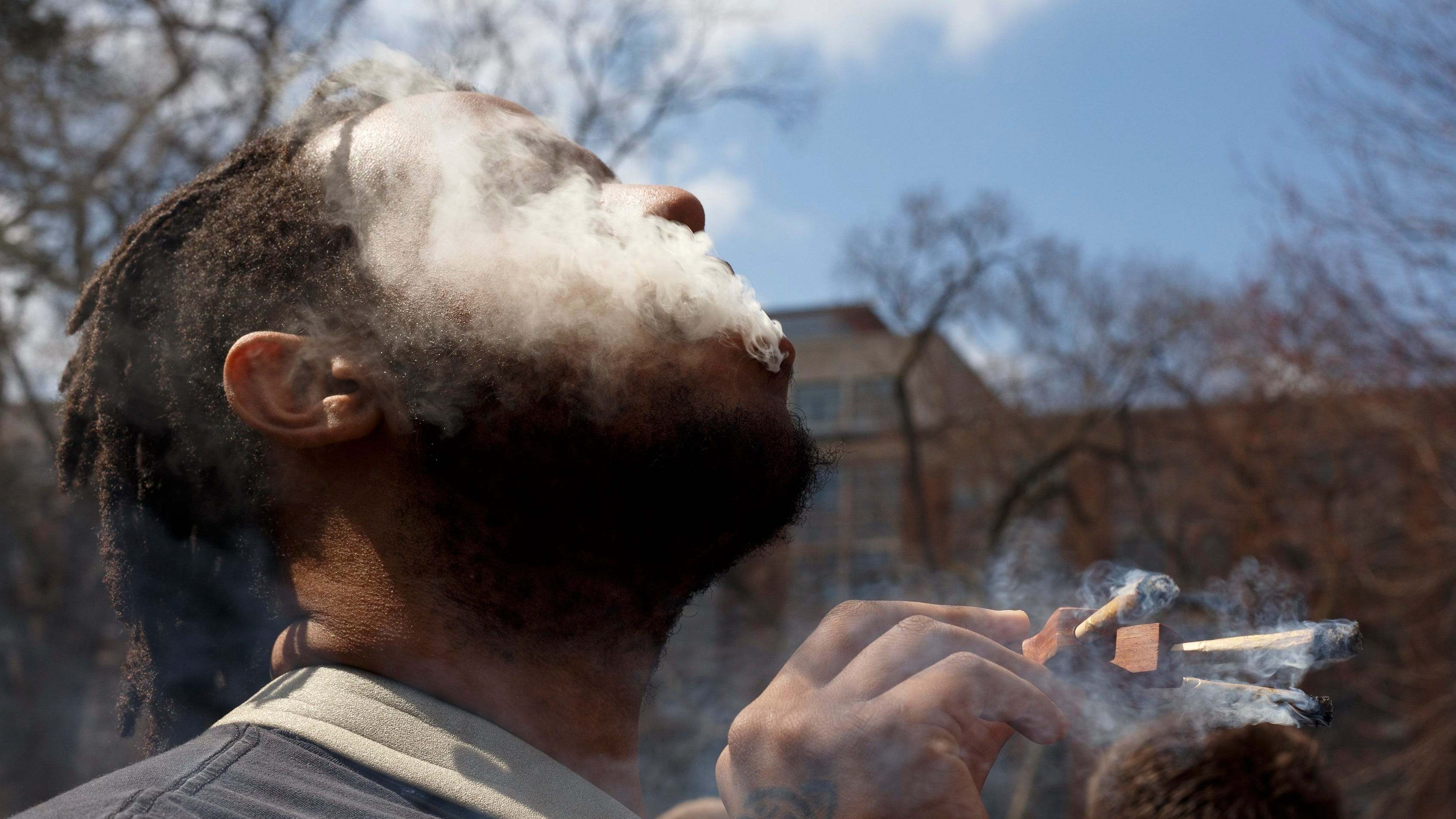 An attendee takes a drag from three joints during...