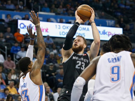 Detroit Pistons forward Blake Griffin (23) shoots between Oklahoma City Thunder forwardx Paul George, left, and Jerami Grant (9) during the first half of an NBA basketball game Friday, April 5, 2019, in Oklahoma City.