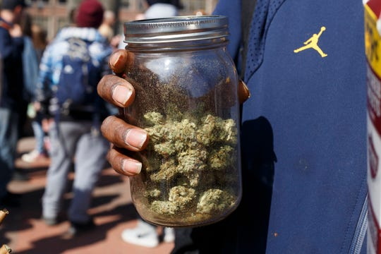 An attendee holds a glass jar filled with marijuana during the 48th annual Hash Bash on Saturday, April 6, 2019 at U-M's Diag in Ann Arbor.