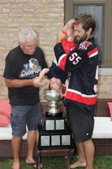 Matt Ford holds his son, Bennett, over the Calder Cup trophy.