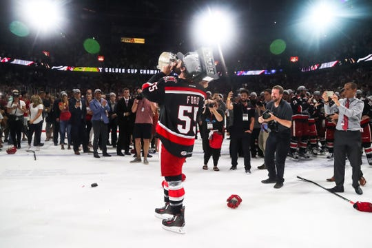 Matt Ford, of the Grand Rapids Griffins of the AHL, holds up the Calder Cup trophy after the Griffins won it in 2017.