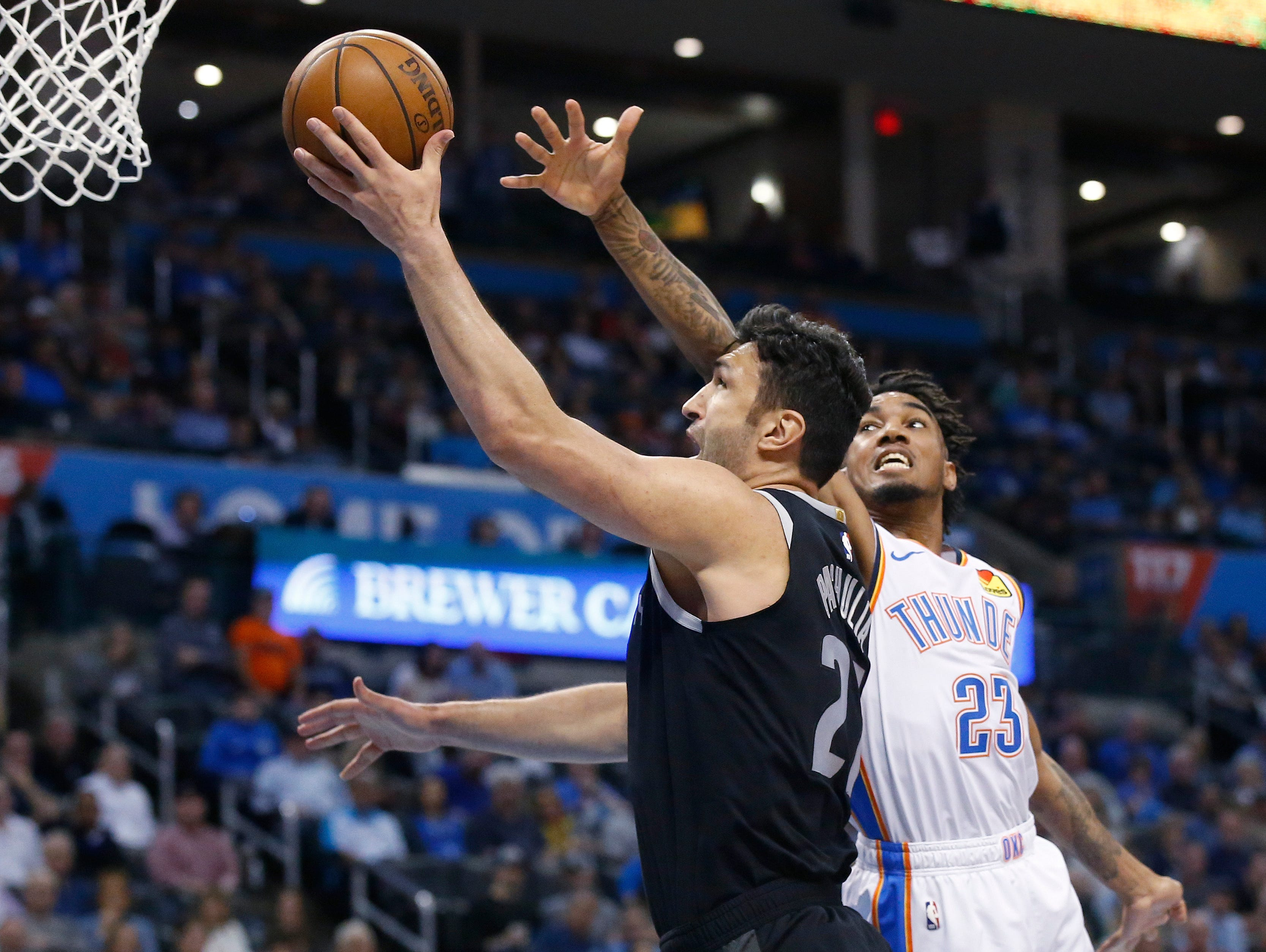 Detroit Pistons center Zaza Pachulia, left, shoots in front of Oklahoma City Thunder guard Terrance Ferguson (23) during the first half.