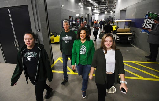 Governor of Michigan Gretchen Whitmer and her family, husband Marc Mallory and daughters Marc Mallory make their way through the halls under the stadium before the start of the semi-finals games at U.S. Bank Stadium.