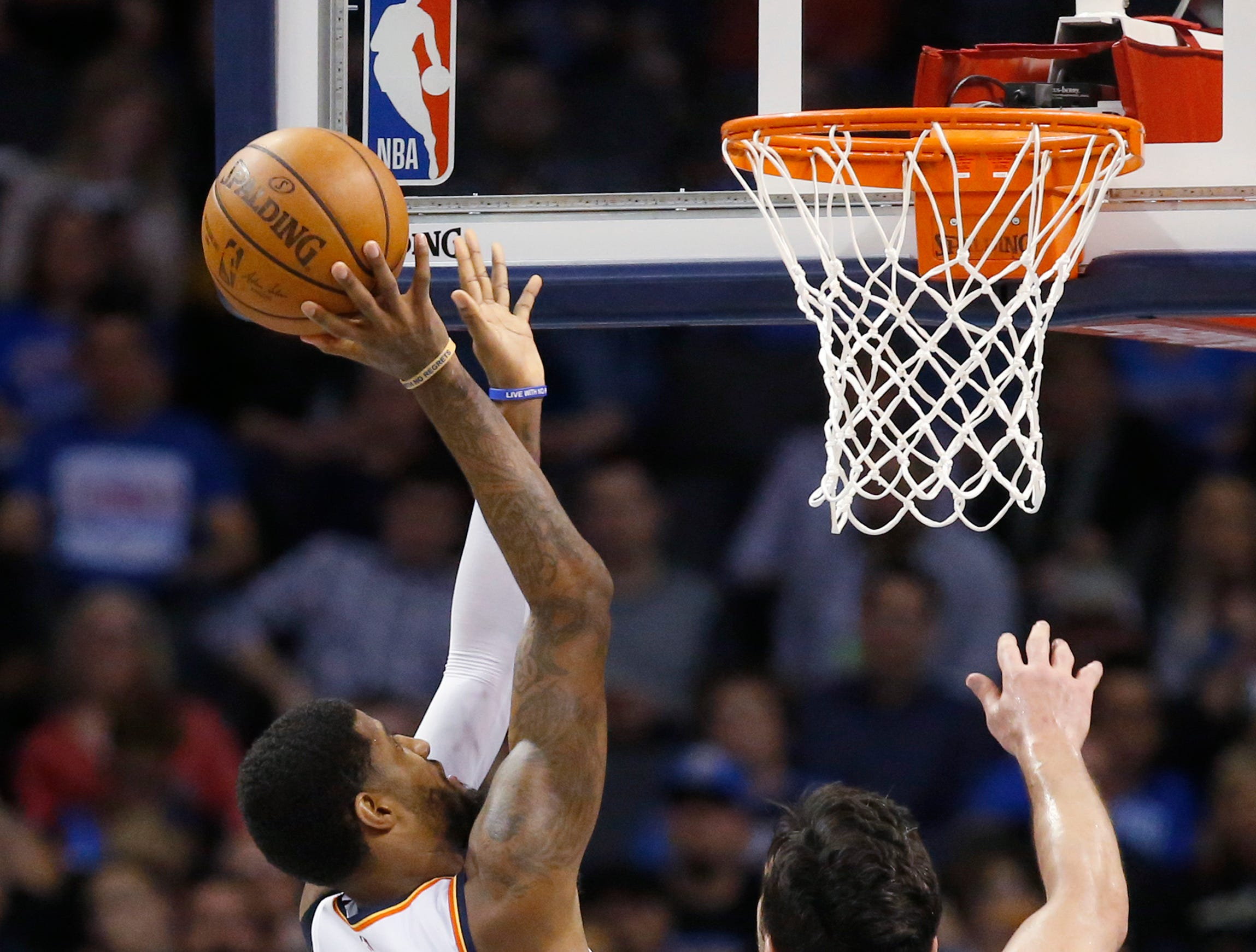 Oklahoma City Thunder forward Paul George, left, shoots in front of teammate Markieff Morris (5) and Detroit Pistons center Zaza Pachulia (27) during the first half.
