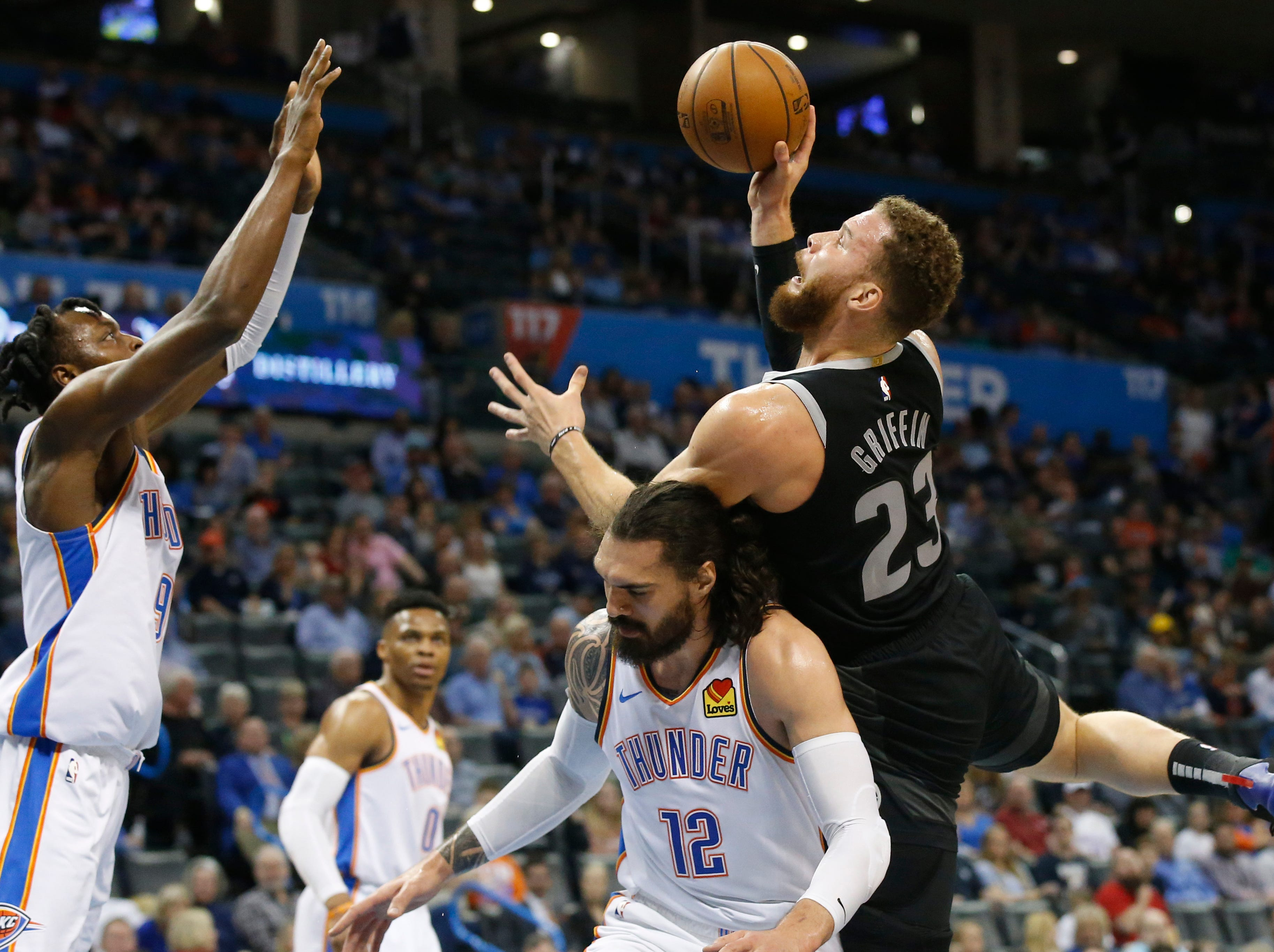 Detroit Pistons forward Blake Griffin (23) is fouled by Oklahoma City Thunder center Steven Adams (12) as he shoots in front of forward Jerami Grant, left, during the first half.