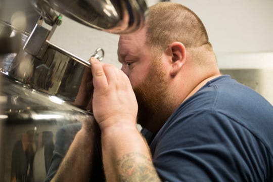 Brewer Joshua Pietrowski peeps inside the boil kettle while brewing an english bitter Friday, April 5, 2019. It was the first time brewing after taking ownership of the Evansville Brewhouse earlier this month. A grand opening is set for First Friday on May 3rd in the Haynie's Corner Arts District.