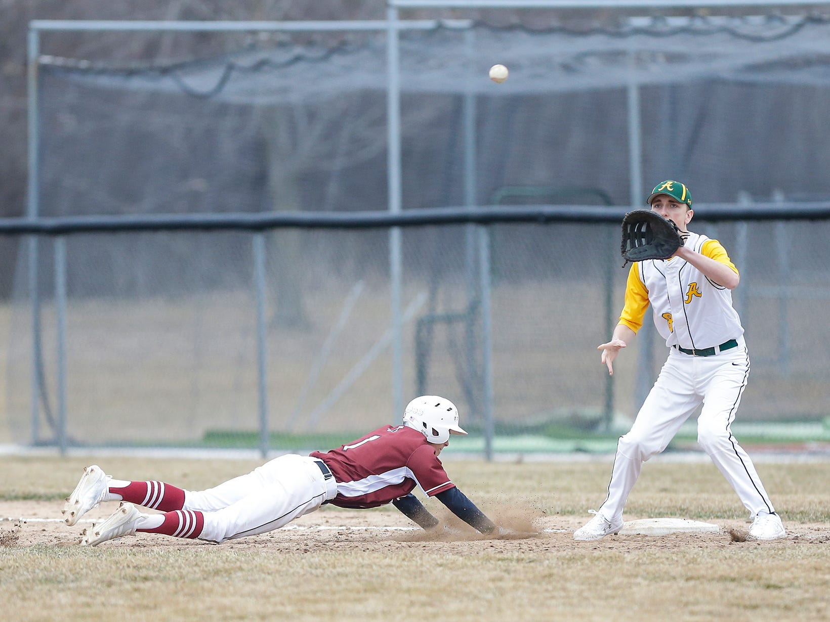Fond du Lac High School baseball's Caden Krug (1) dives back to first to avoid a tag by Ashwaubenon High School's Ben Wendorf (8) Saturday, April 6, 2019 during their game in Fond du Lac, Wis. Fond du Lac won the game 5-3. Doug Raflik/USA TODAY NETWORK-Wisconsin